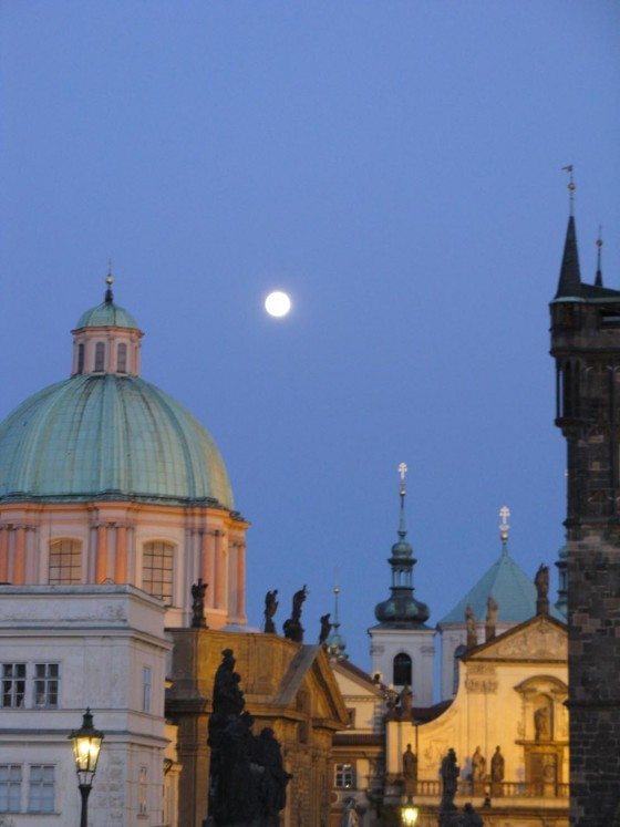 The full moon rising over Prague, as seen from the Charles Bridge.