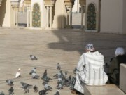 Man and Woman feeding pigeons at Hassan II Mosque Casablanca Morocco