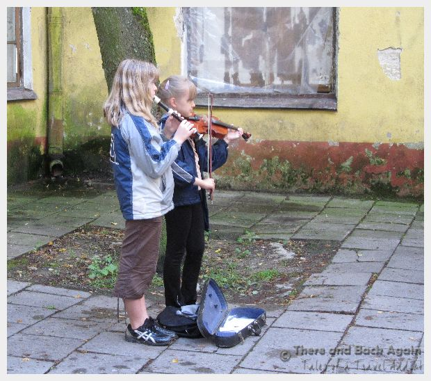 Little girls playing the violin for money on the street, Talinn, Estonia.